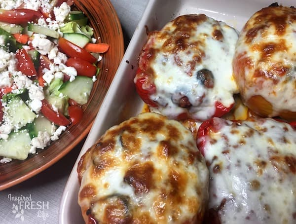Ultimate Pizza Stuffed Peppers in baking pan next to tossed salad