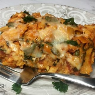 A slice of butternut squash pasta bake on a plate with a fork
