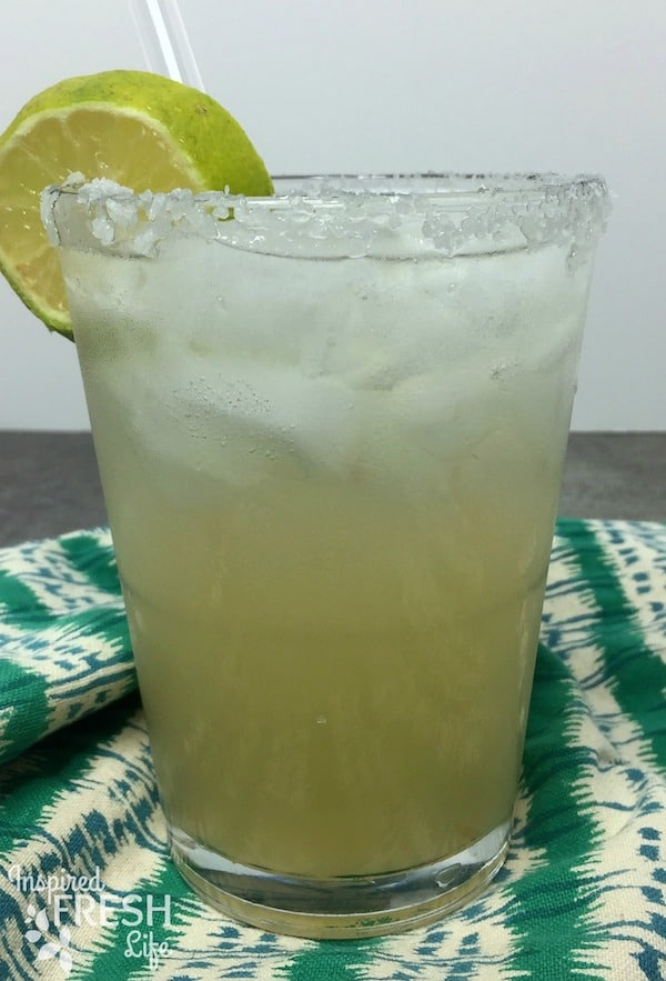 A Paloma cocktail with a salted rim and lime wheel on a green and white patterened towel.