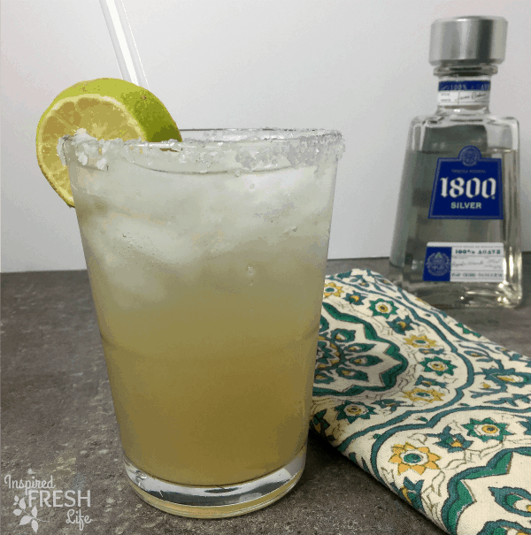 A Paloma cocktail in a salted rim glass with a bottle of tequila in the background.