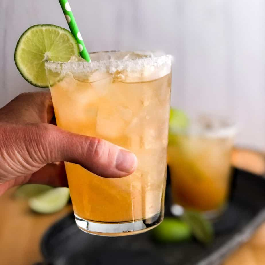 Hand holding a Paloma garnished with a salted rim and a lime wheel.