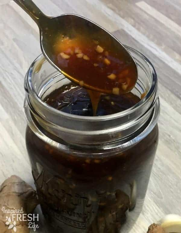 A spoon of Homemade Teriyaki Sauce dripping into the remaining sauce in a mason jar.