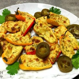 Spicy Cream Cheese Stuffed Mini Peppers on a white plate garnished with jalapenos and cilantro