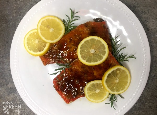 Teriyaki Salmon with Rosemary fillets on a white plate garnished with lemon and rosemary sprigs.