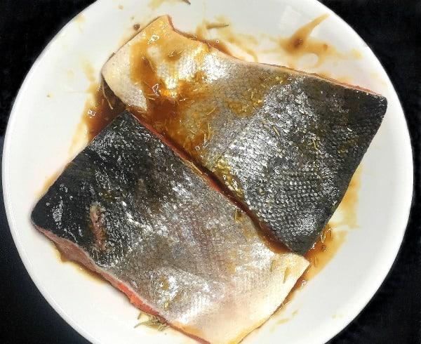 Teriyaki Rosemary Salmon marinating in a white bowl.