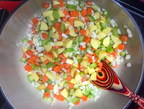 Veggies cooking in a Dutch oven to make Ham and Bean soup.