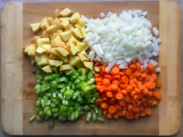 Diced carrots, celery, onion, and potato on a wood cutting board.