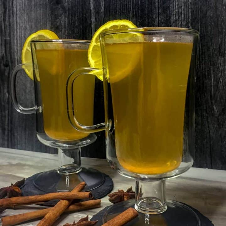 Spiced Hot Toddy with a lemon wheel garnish and cinnamon sticks and star anise at the base.