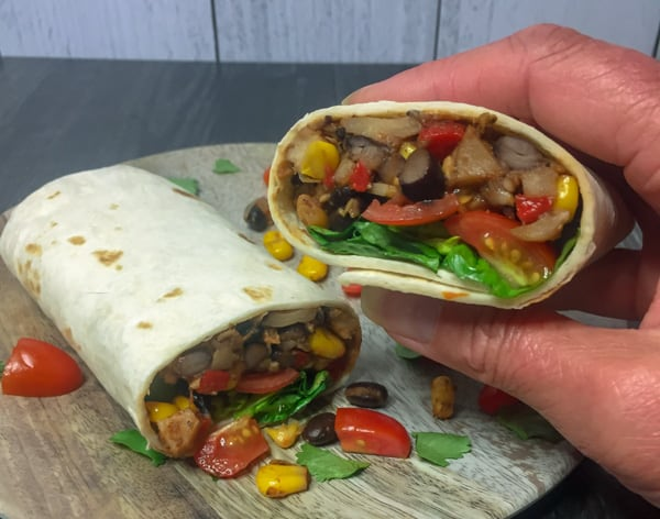 Vegetarian Burrito on a wood grain plate with hand holding half the burrito.