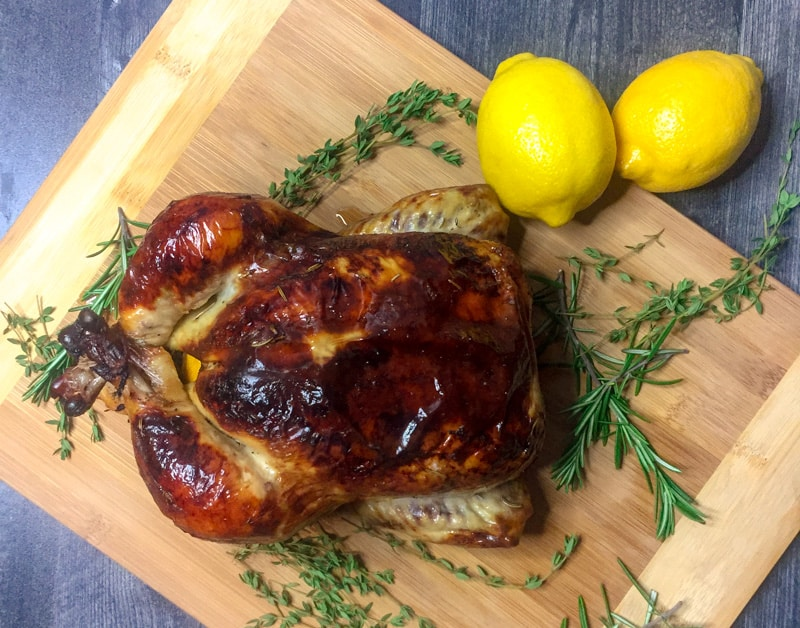 Roasted chicken on a wood cutting board with fresh rosemary, thyme, and lemons as garnish.