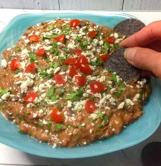 Fiesta Black Bean Dip in a blue bowl with fingers holding a chip.