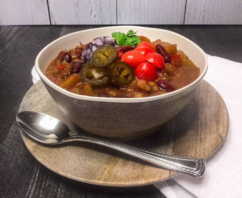 Vegetarian Chili in a faux wood bowl garnished with tomatoes, cilantro, red onion, and jalapenos.