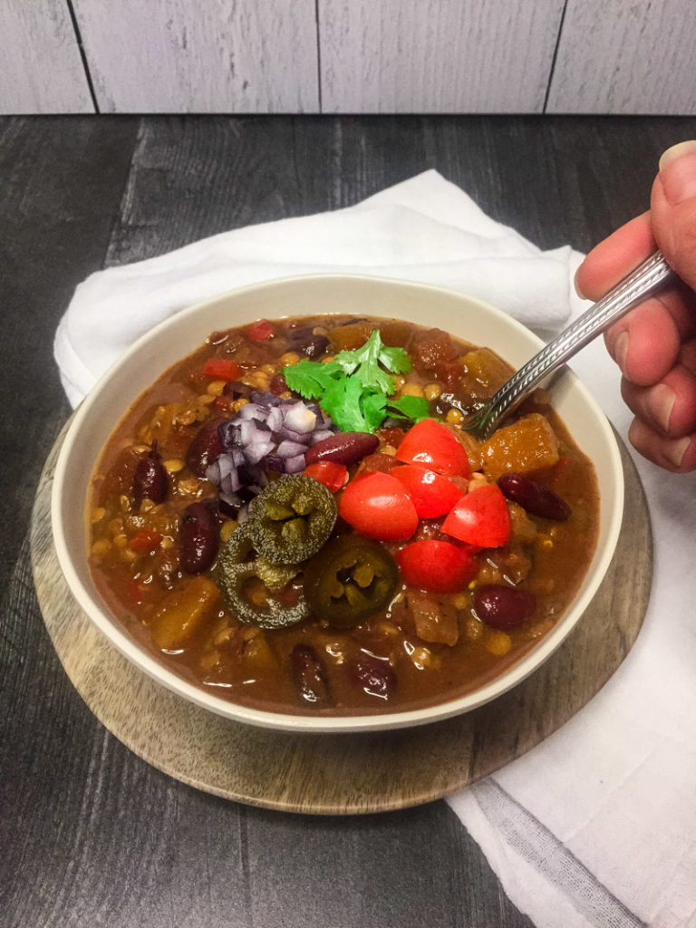 Close up of Vegetarian Chili in a faux wood bowl, on a white dish towel, with a hand holding a spoo--garnished with tomatoes, cilantro, red onion, and jalapenos.