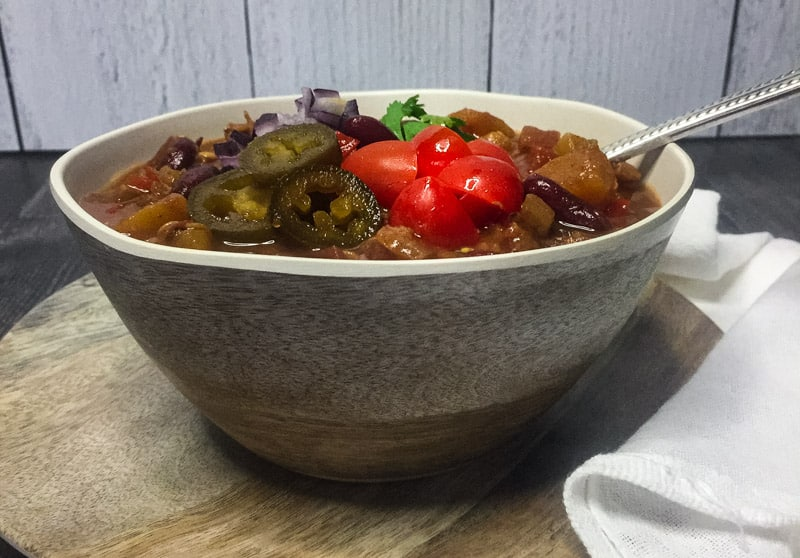 Close up of Vegetarian Chili in a faux wood bowl garnished with tomatoes, cilantro, red onion, and jalapenos.