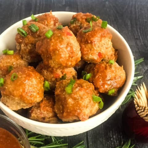 BBQ Turkey Meatballs in a white bowl with chopped chive garnish.