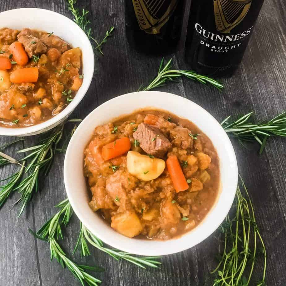 Irish Beef Stew in white bowls garnished with rosemary and thyme with Guinness can in background.