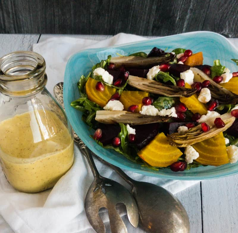 Roasted Beet and Endive Salad in a blue bowl with dressing bottle to right and silver salad spoons laying in bewteen.