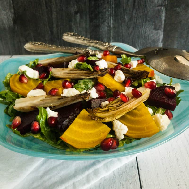 Roasted Beet and Endive Salad in a blue bowl with silver salad spoons resting on top.