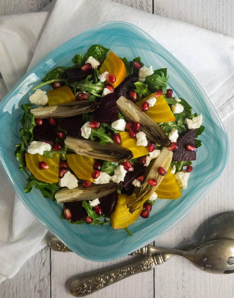 Top shot of Roasted Beet and Endive Salad in a blue bow with silver salad spoons laying in front.