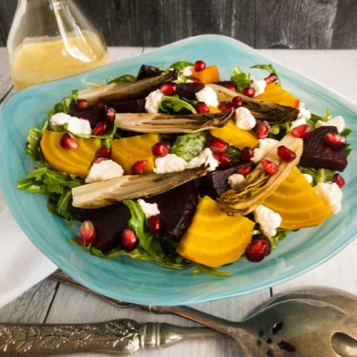 Roasted Beet and Endive Salad in a blue bowl with a dressing bottle in the back and silver salad spoons in front.