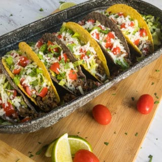 Yellow and blue corn taco shells stuffed with meat, lettuce, tomato, and manchego cheese.