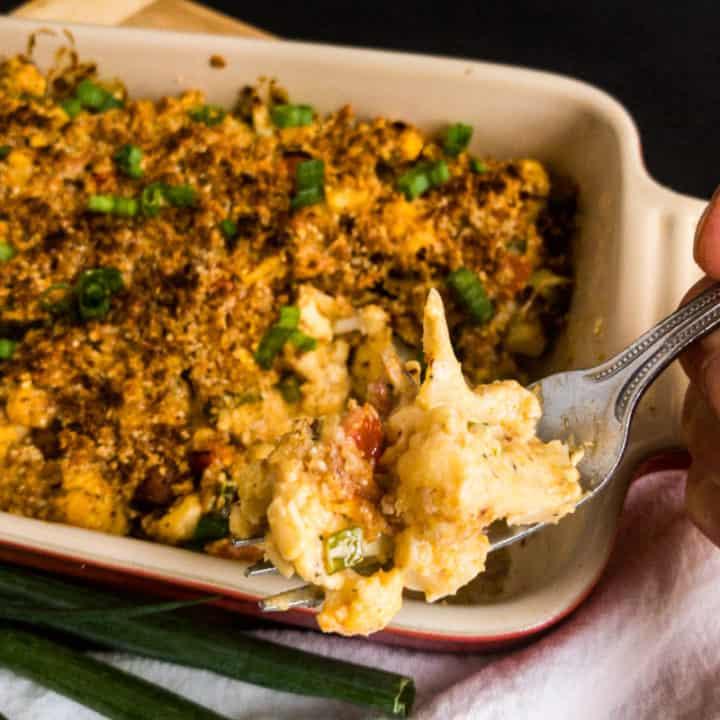 A bite of Cheesy Cauliflower Casserole above the casserole dish.