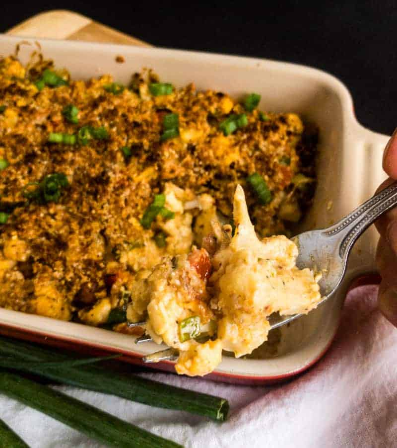 A bite of Cheesy Cauliflower Casserole above the casserole dish.