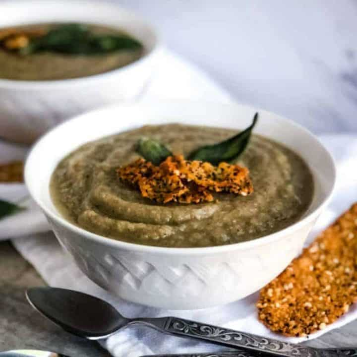 Creamy Celeriac Soup in a white bowl garnished with fried sage leaves and everyting parmesan crisps.
