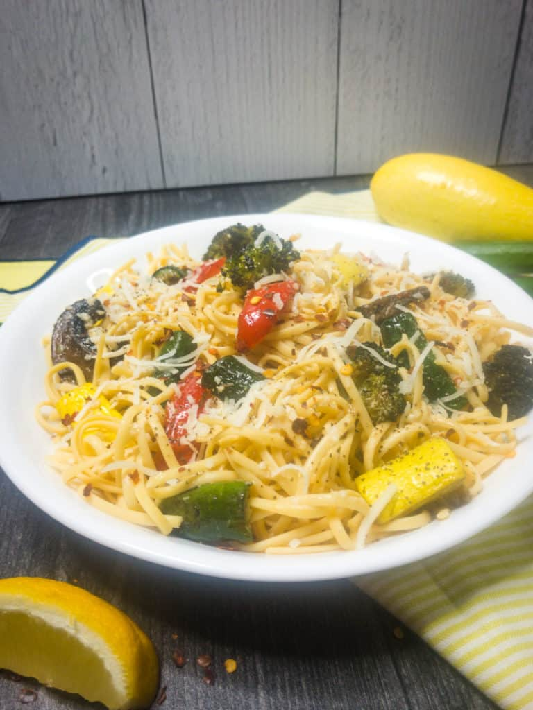 Roasted Vegetable Primavera in a white pasta bowl surrounded by yellow squash, zucchini, and a yellow linen.