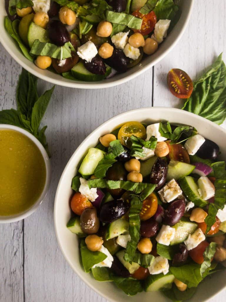 Greek Vinaigrette in a small white bowl between two bowls of Mediterranean Chickpea Salad.
