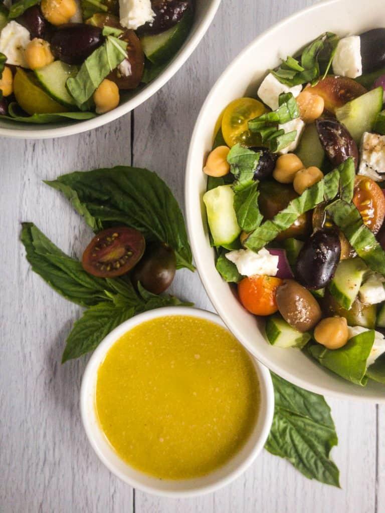 Closeup shot of Greek Vinaigrette next to a Greek Spinach Salad in a white bowl.