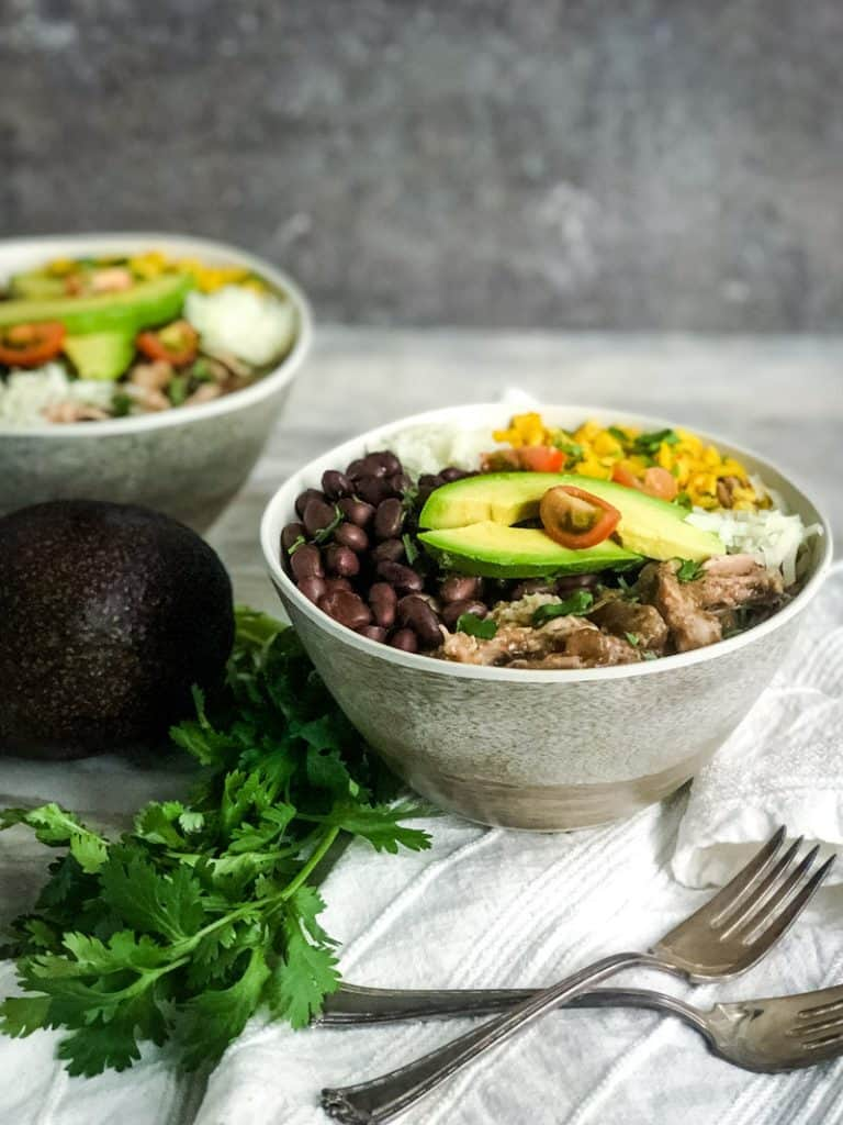 Side shot of two pork carnitas bowls with black beans, yellow rice, manchego cheese, avocado, and tomato.