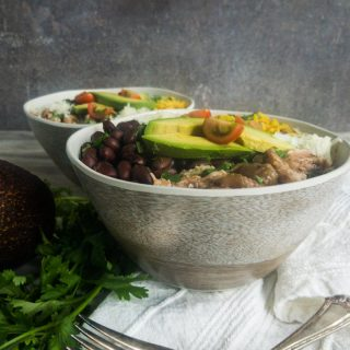 Close up shot of two pork carnitas bowls with black beans, yellow rice, manchego cheese, avocado, and tomato.