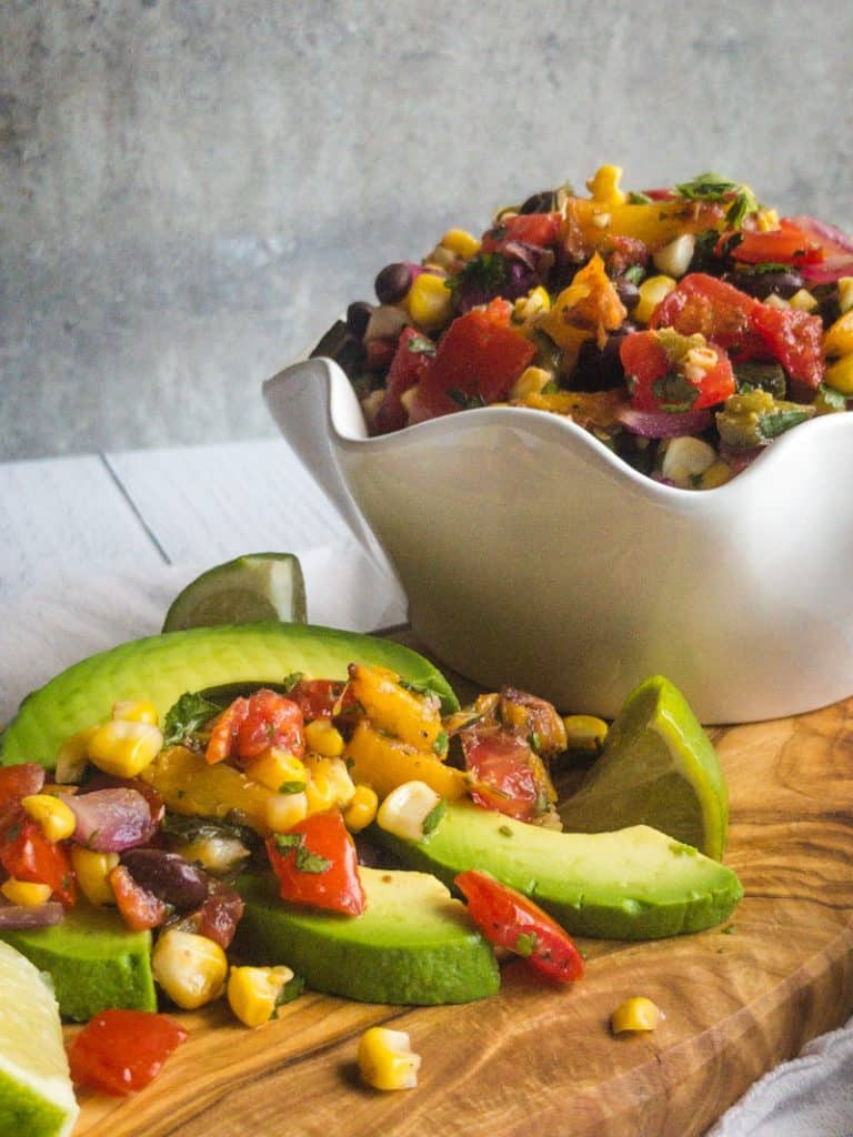 Close up of avocado slices topped with Grilled Summer Corn and Peach Salsa; more salsa in a white bowl in the background.
