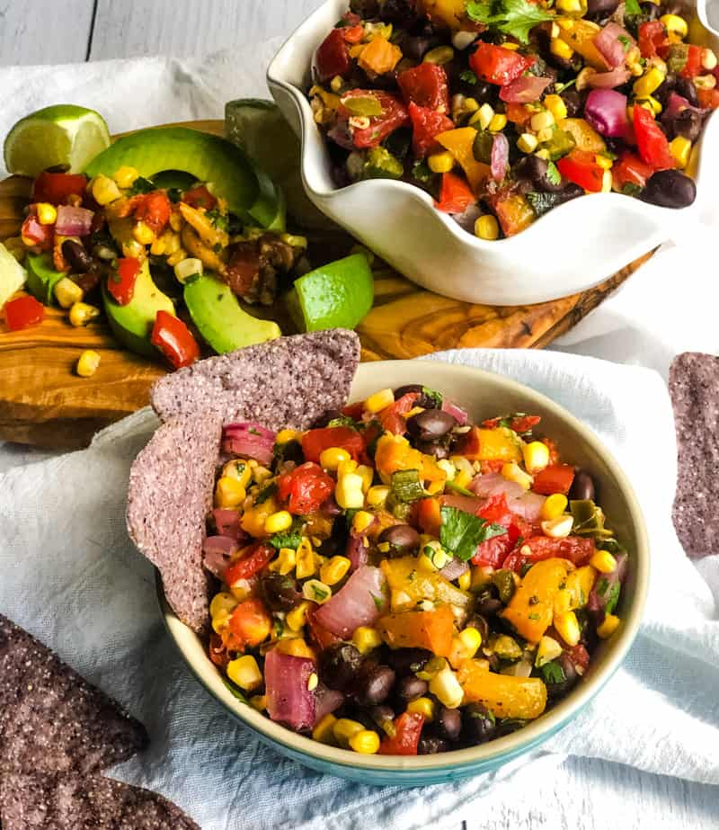Overhead shot of Grilled Summer Corn and Peach Salsa in a white bowl and a blue bowl with a wood cutting board with salsa and avocado slices on it.