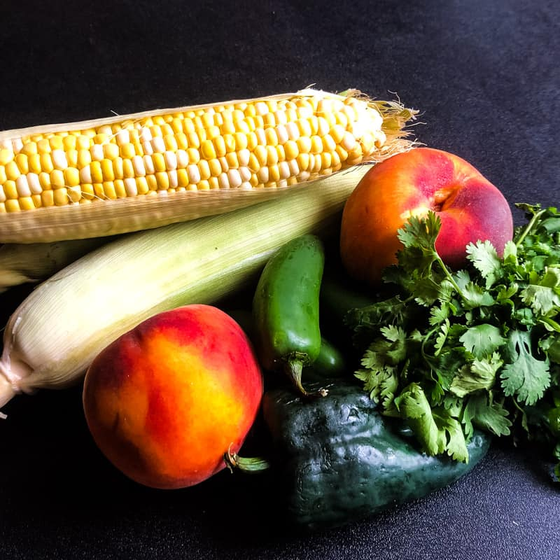 Ingredient shot: corn on the cob, peaches, pablano pepper, jalapenos, and cilantro with a dark background.