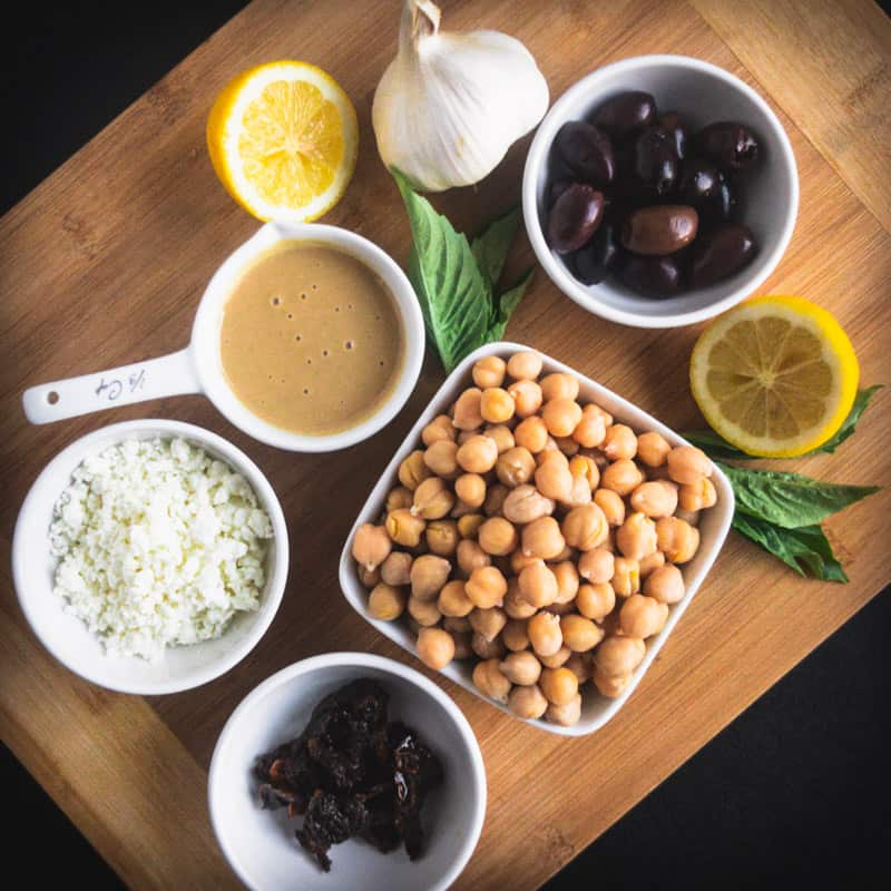 Ingredients for Mediterranean Hummus on a wood cutting board: garlic, tahini, olives, basil, chick peas, feta cheese, lemon, sun-dried tomatoes.