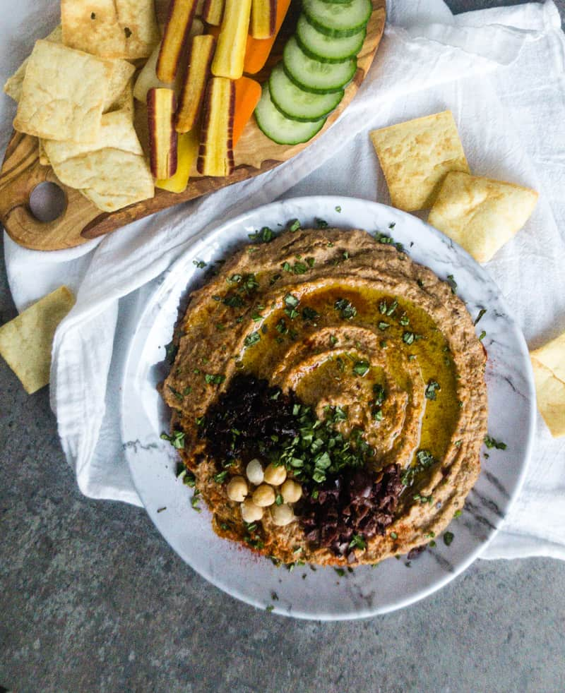 Overhead shot of Mediterranean Hummus on a faux marble plate garnished with olives, chickpeas, basil, and sun-dried tomatoes.