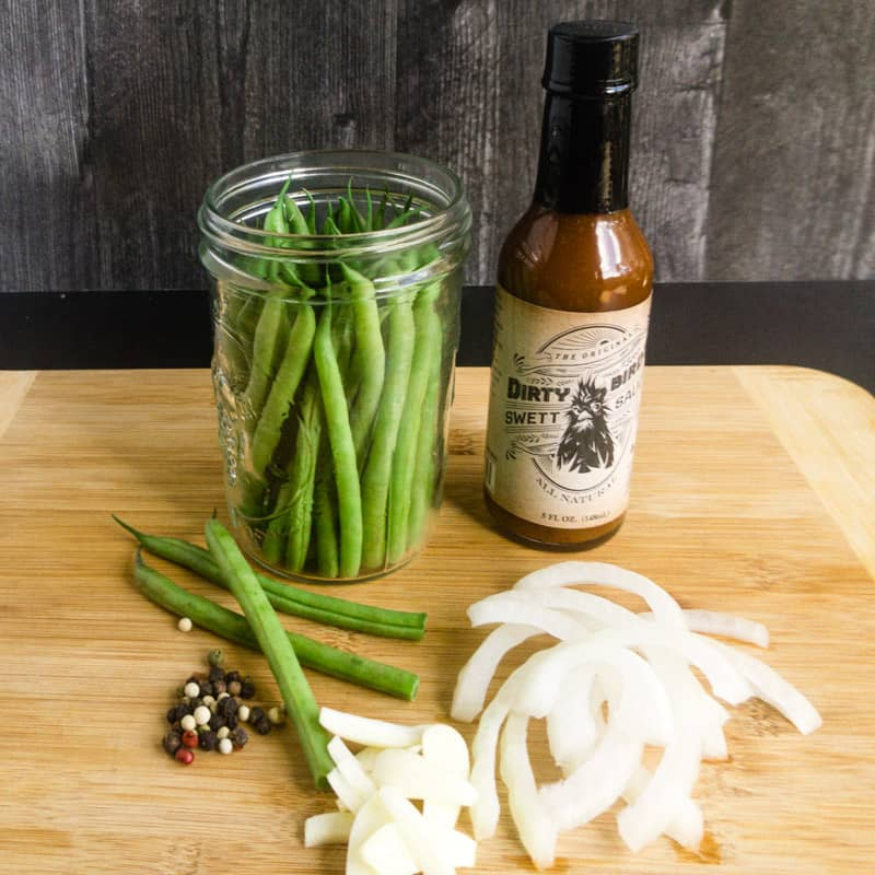 Ingredients for Quick Pickled Green Beans on a wood cutting board next to a jar of Swett Sauce.