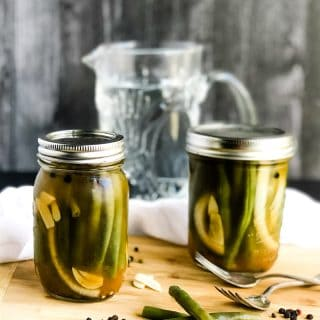 Two jars of Quick Pickled Green Beans on a wood cutting board with beans, peppercorns, and sliced garlic scattered.