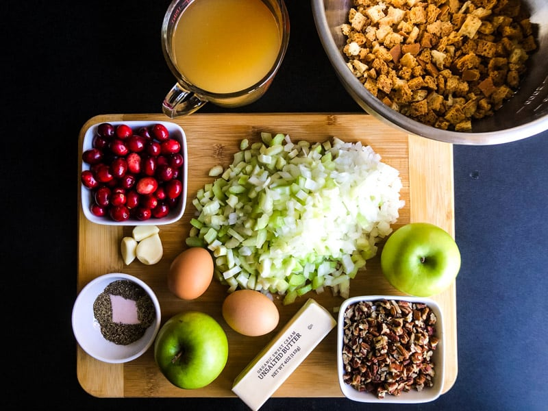 Ingredients prepped for Gluten-free Vegetarian Stuffing on a wood cutting board.