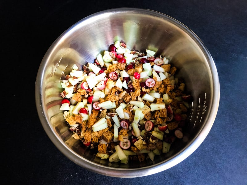 Apples, cranberries, pecans, and bread cubes in a stainless steel bowl.
