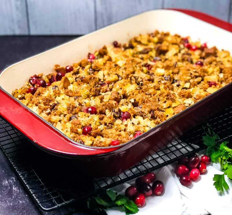Gluten-free Vegetarian Stuffing casserole on a cooling rack with fresh cranberry and parsley garnish.