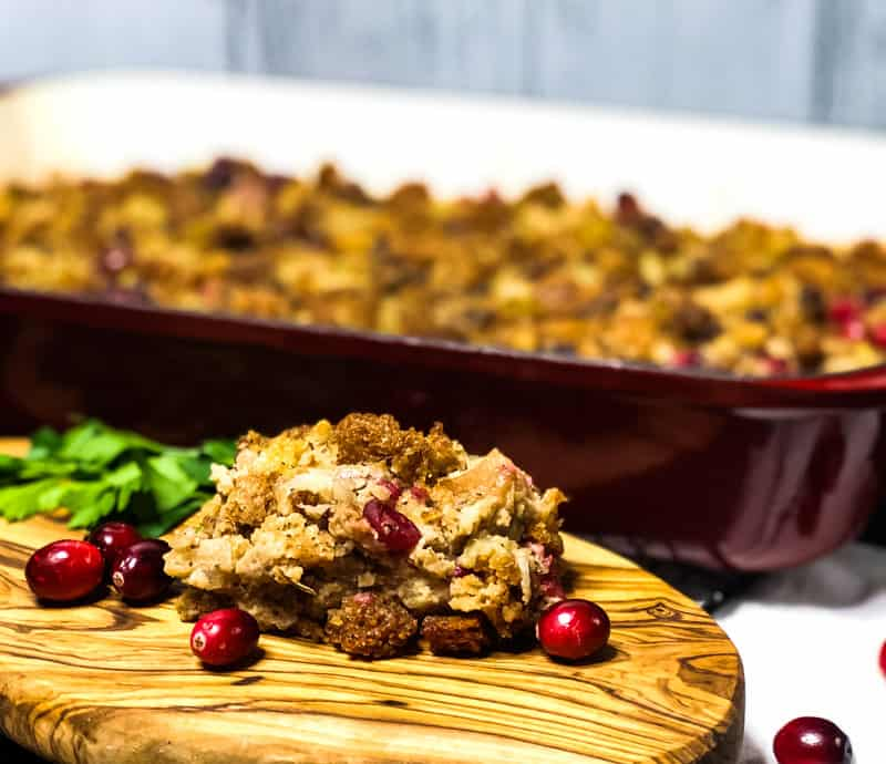 A bite of Gluten-free Vegetarian Stuffing on a wood platter in front of the casserole dish with cranberry and parsley garnish