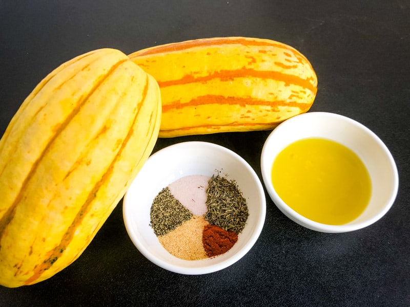 Whole delicata squash with seasonings and olive oil in prep bowls on a black surface