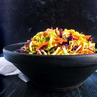 Close up shot of Brussels Sprouts Coleslaw in a black bowl.