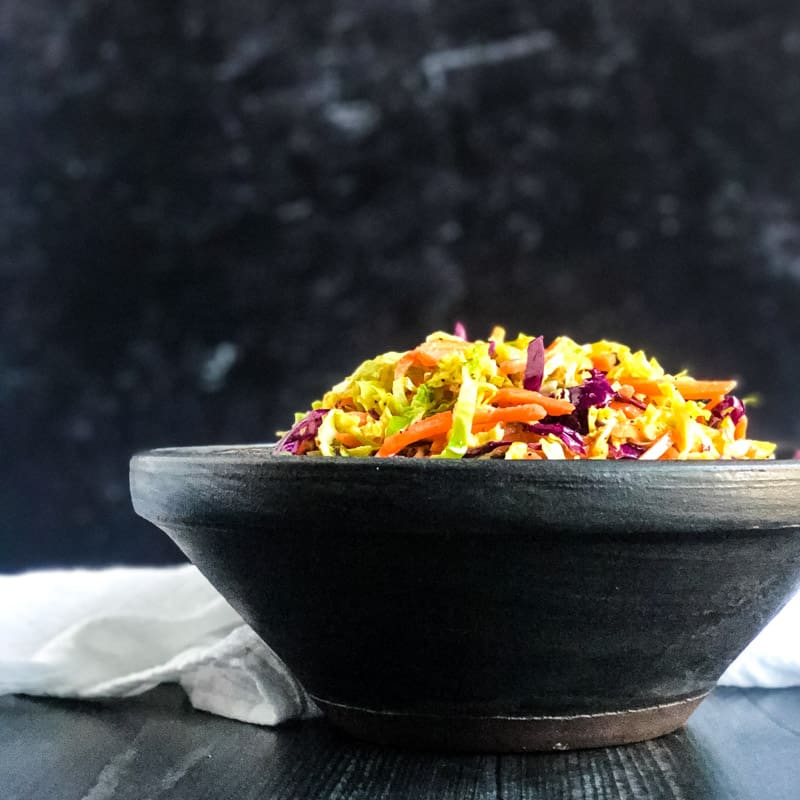 Side shot of Brussels Sprouts Coleslaw in a black bowl.