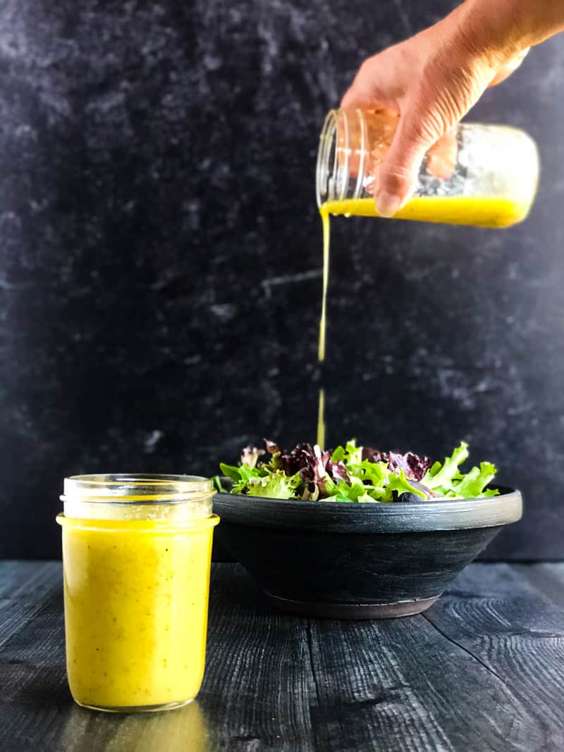 Jar of Creamy Lemon Honey Dijon Vinaigrette in foreground with mixed green salad in background with hand pouring a jar of vinaigrette over the salad.