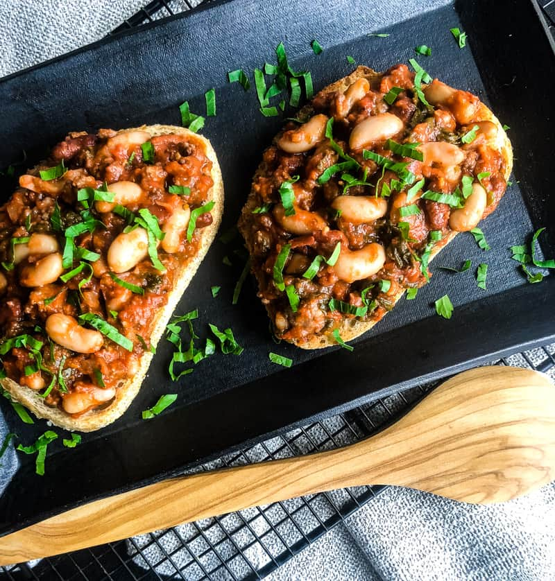 Beans and Sausage on Toast on a black platter garnished with parsley with wooden spoon in foreground.