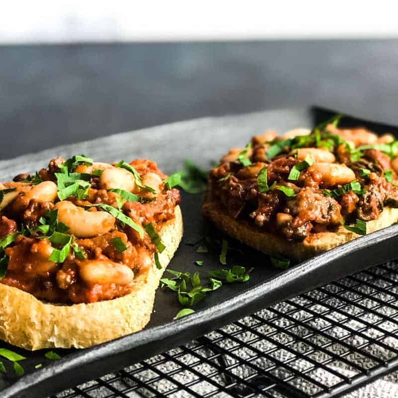 Beans and Sausage on crusty sourdough bread on black platter garnished with parsley.